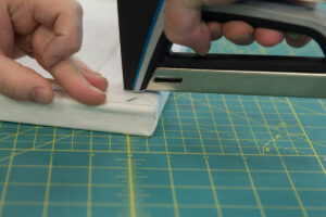 Holding down the folded fabric to staple at the corner