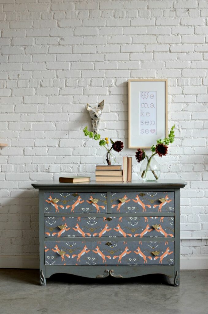 Barb Blair of Knack Studios shows us how to refresh an old dresser using this Foxy wallpaper designed by Holli Zollinger