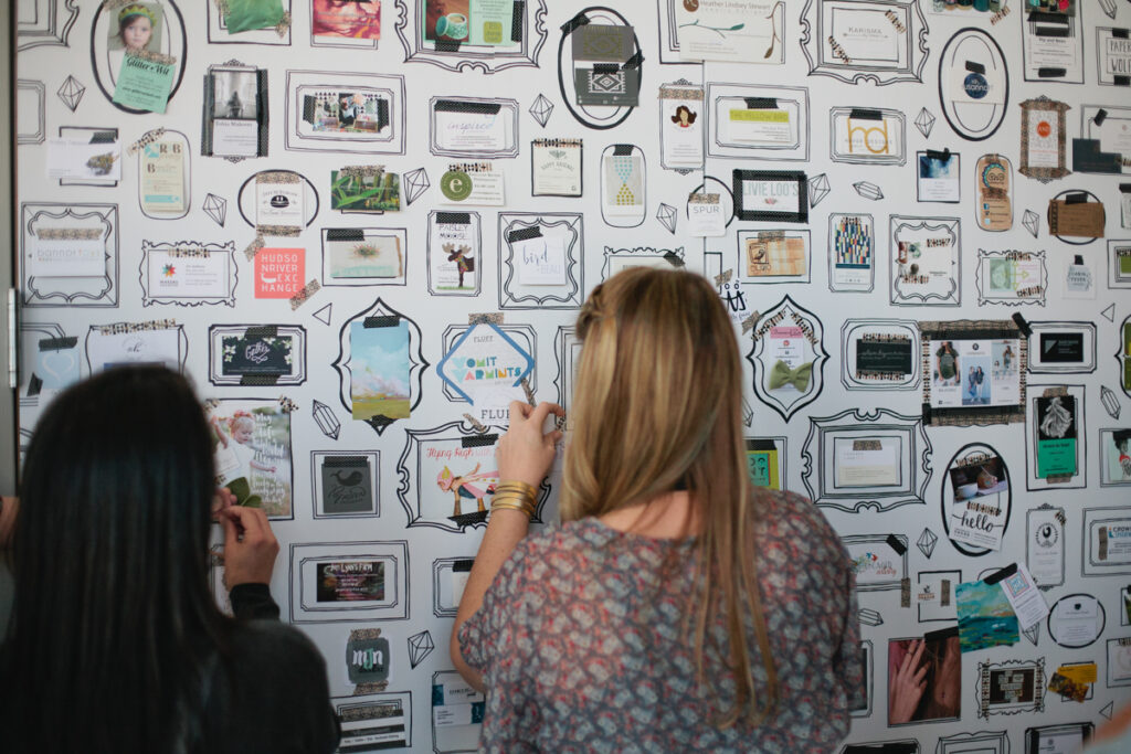 Girls adding business cards to Spoonflower's wallpaper wall at Makers Summit 2016