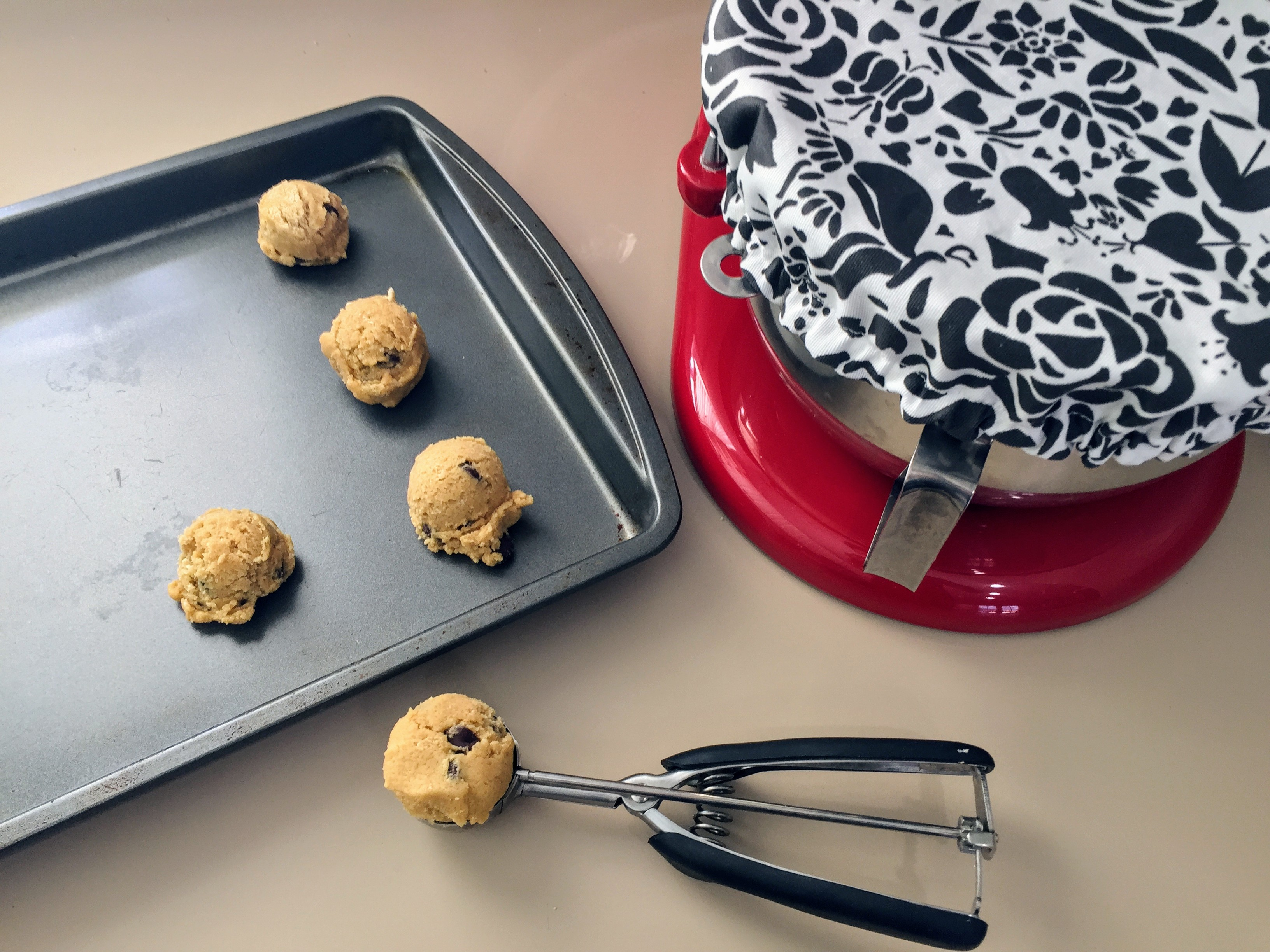 Bowl cover on red Kitchenaid mixer next to cookie dough