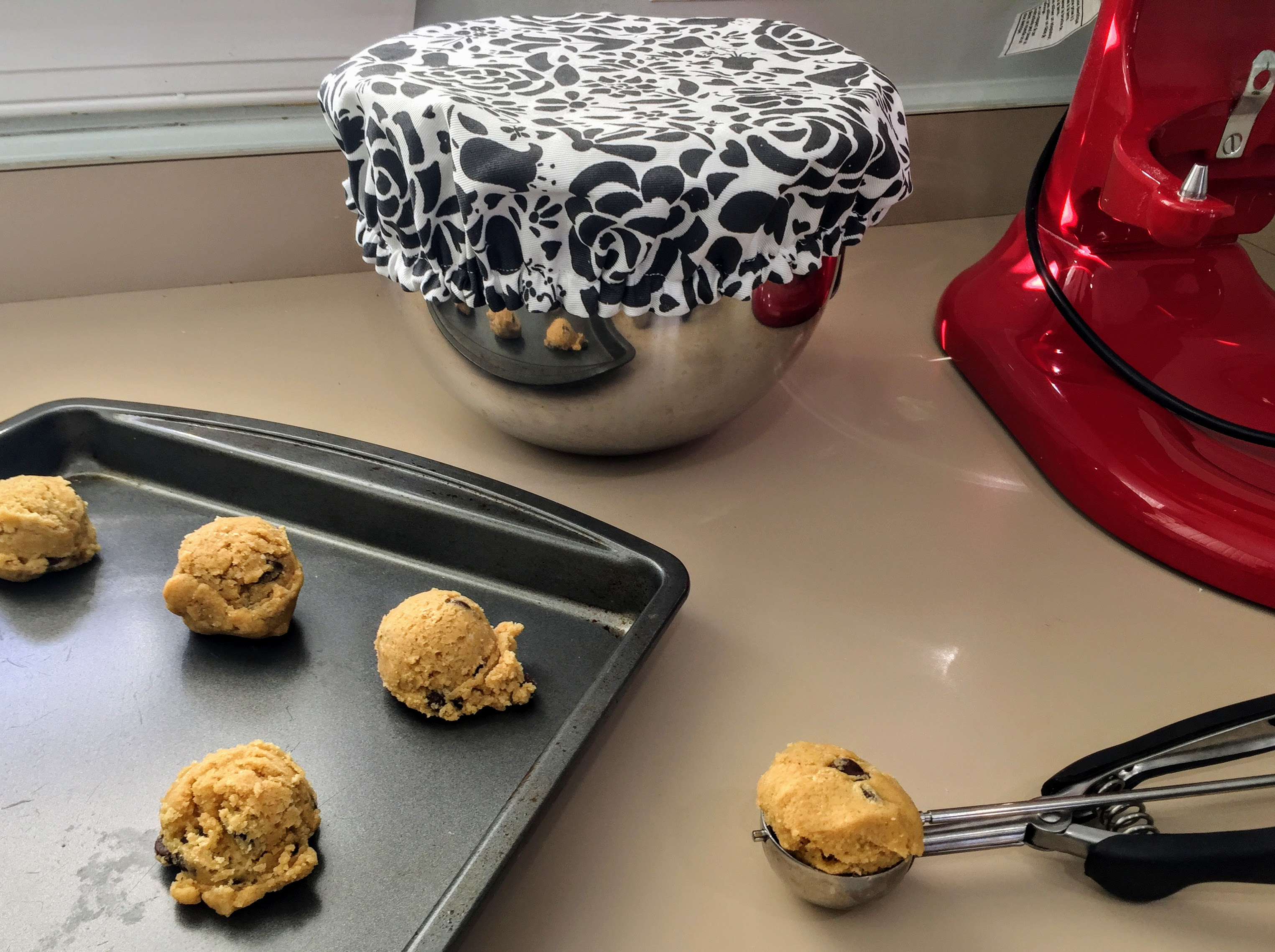 DIY cover on stationary mixer bowl beside cookie dough on tray