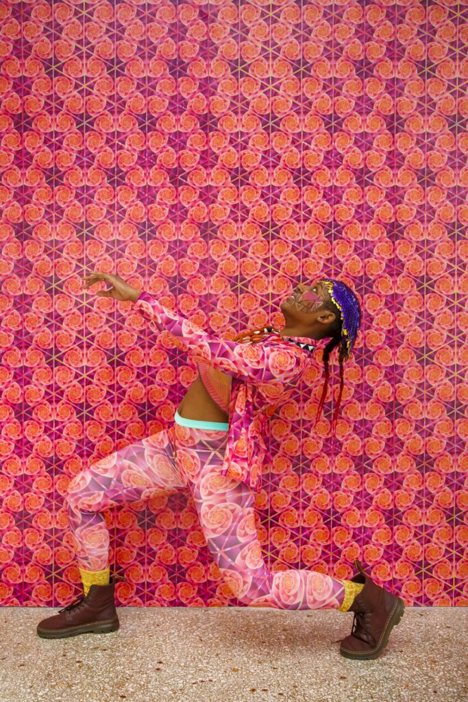 Colorful outfit worn by a model with face paint in front of bright pink geometric wallpaper | Spoonflower Blog