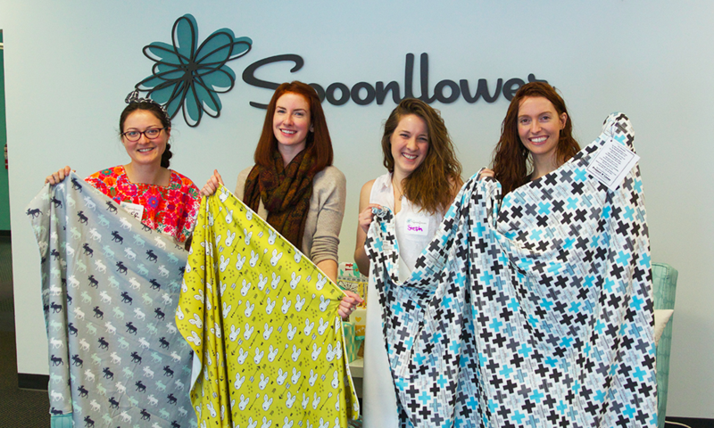 Spoonflower employees show off their handmade Organic Cotton Knit blankets that will be donated to our local Project Linus chapter. | Spoonflower Blog