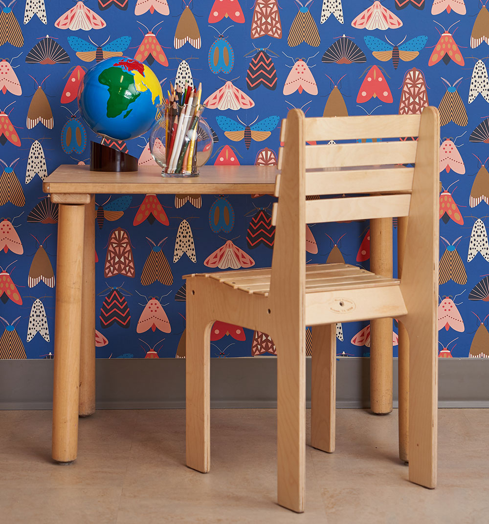 A kid size desk in front of colorful moth and butterfly wallpaper