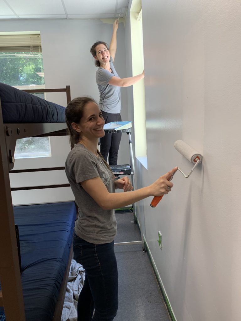 Marketing team members Alexis and Meredith work quickly to paint the walls before the rest of the room transformation can take place. | Spoonflower Blog