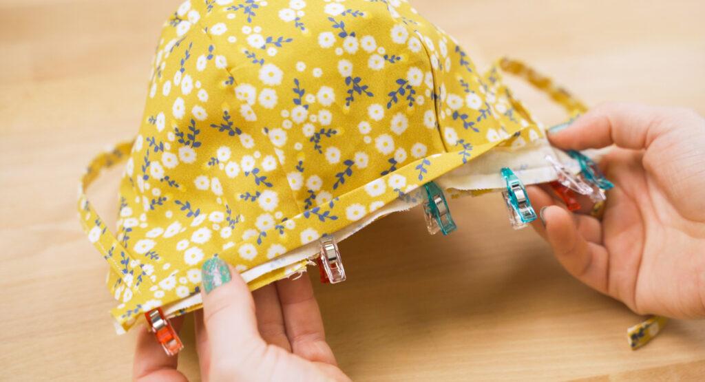 Nähe das Einfassband an die Mütze mit 0,5 cm Nahtzugabe. Lasse hierbei  ca 1 cm Band überstehen an jedem Ende. Die rechte Seite des Einfassbandes sollte auf der Futterseite liegen.