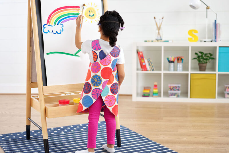 Girl painting a rainbow on an easel while wearing a handmade, colorful art smock