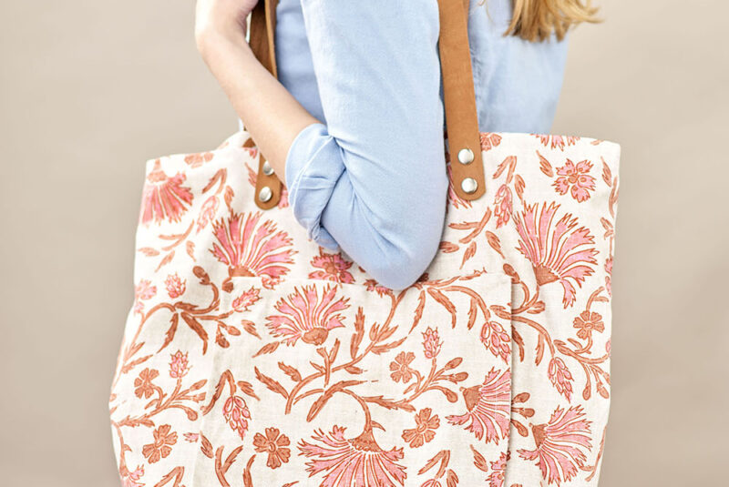A women carries a handmade tote bag with a classical floral print