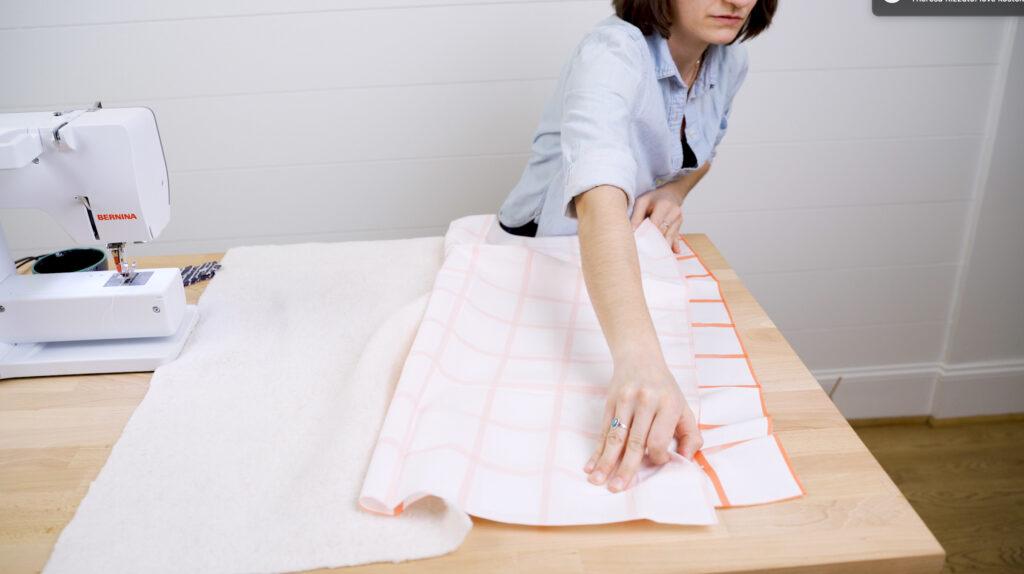 Nehme das Rückteil und falte es in der Mitte, rechten Seiten zusammen. Schneide ein passendes Stück Wattierung hinzu.