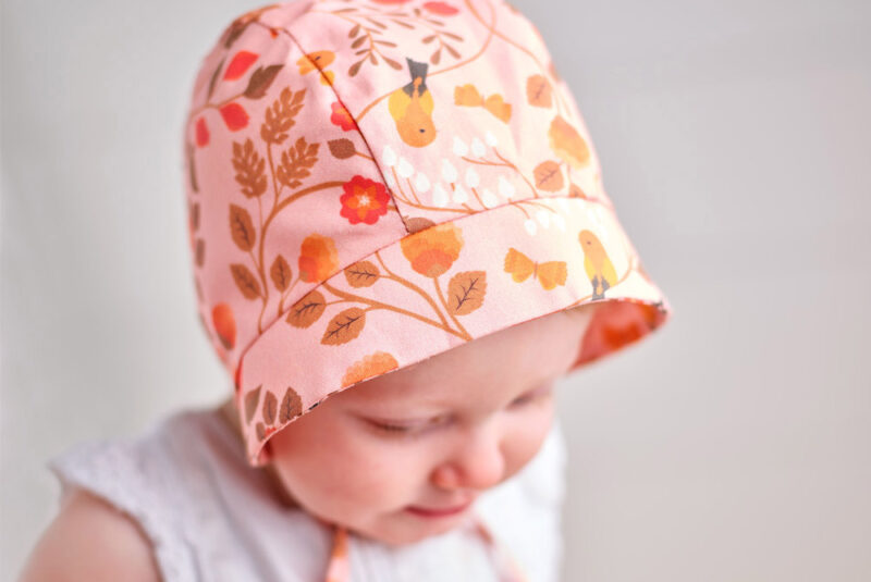 Baby wearing a pink bonnet with a ditsy floral design