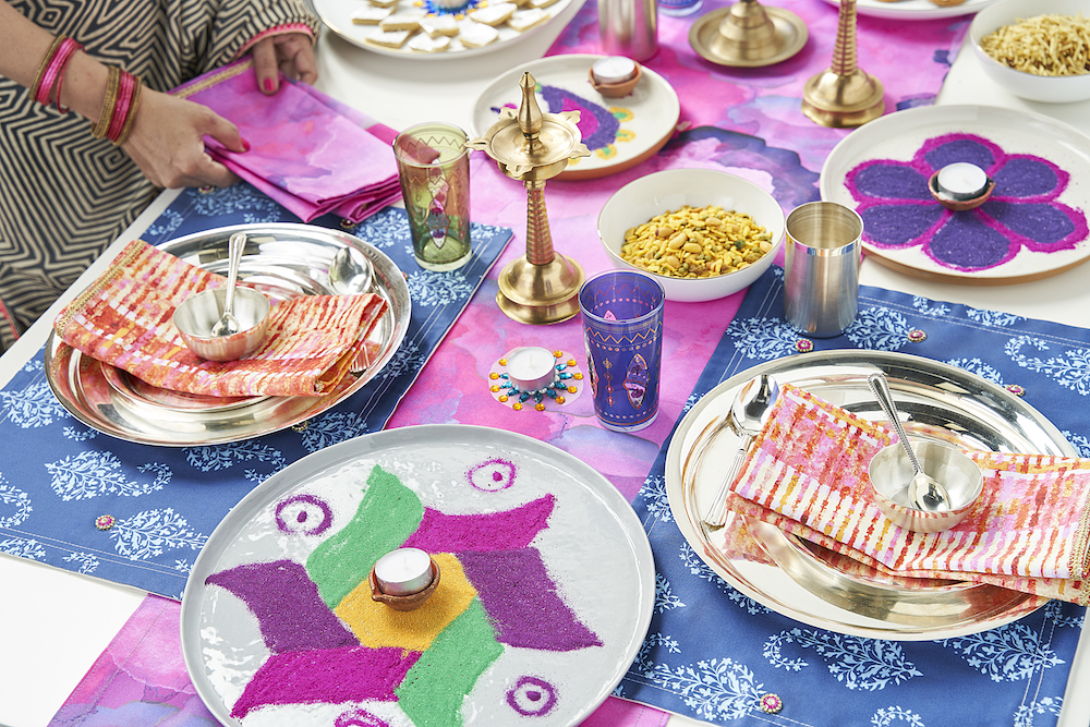 Table runners, placemats and napkins featuring bright, vibrant colors with Indian motifs adorn Anitha's Diwali table setting. | Spoonflower Blog