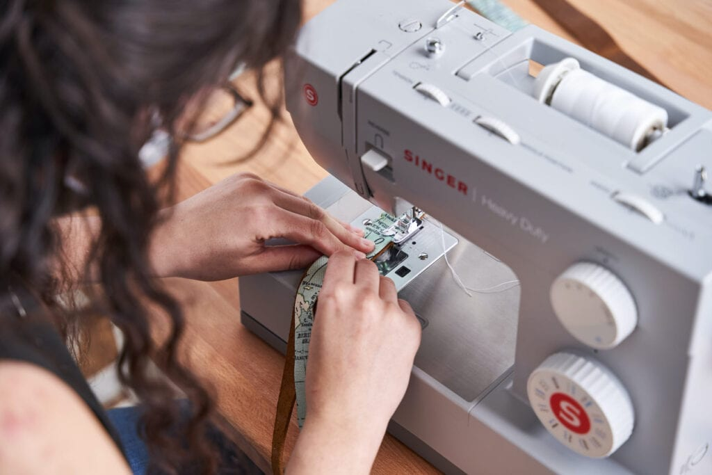 Ace sews the leather and fabric together to create a strap.