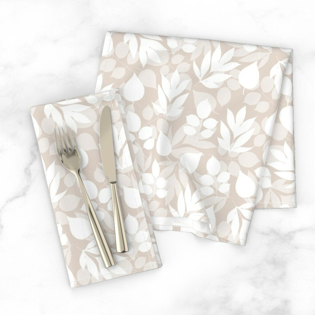 Two folded napkins featuring a cream and white floral pattern