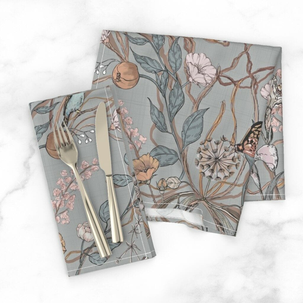 Two folded napkins featuring a grey background with light pink and orange flowers