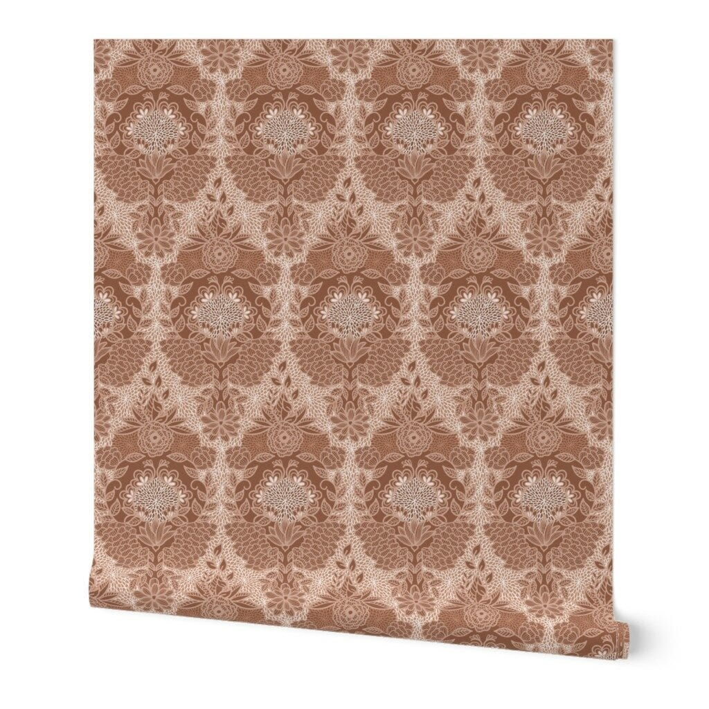 A partially unrolled roll of wallpaper featuring a floral damask design in sienna brown.