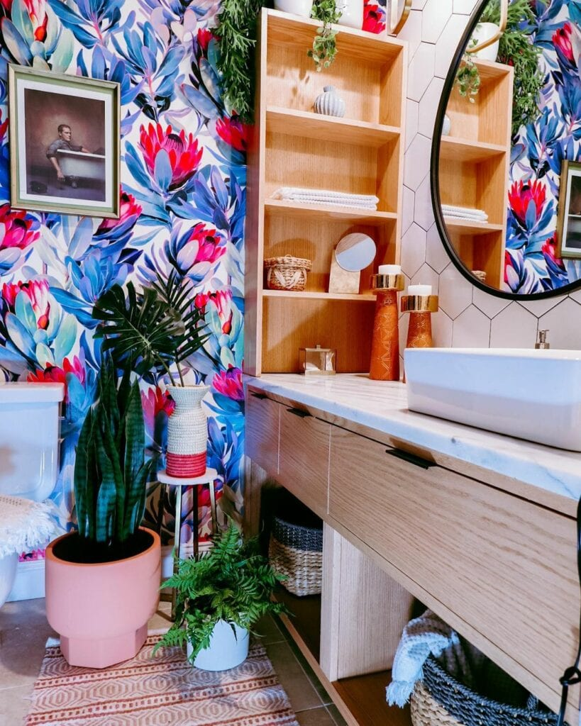 A bathroom features a bold colorful floral wallpaper on one wall
