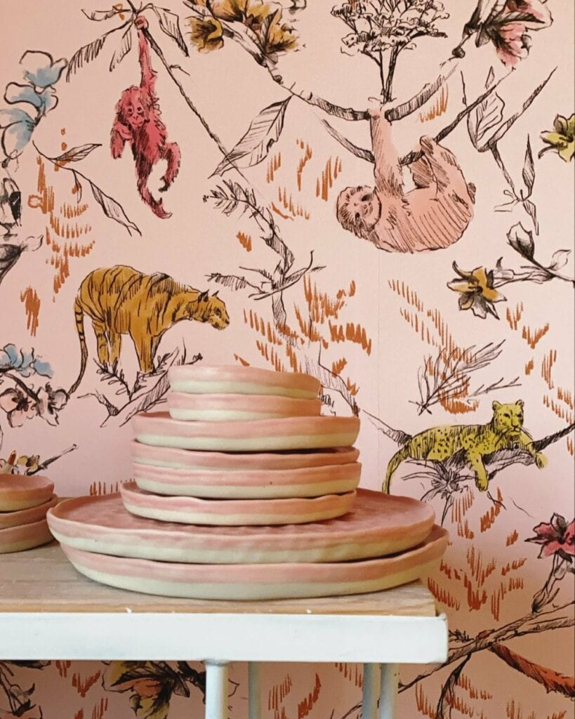 Pink and beige pottery sit in front of a wall wallpapered with a pink and yellow jungle illustrated wallpaper
