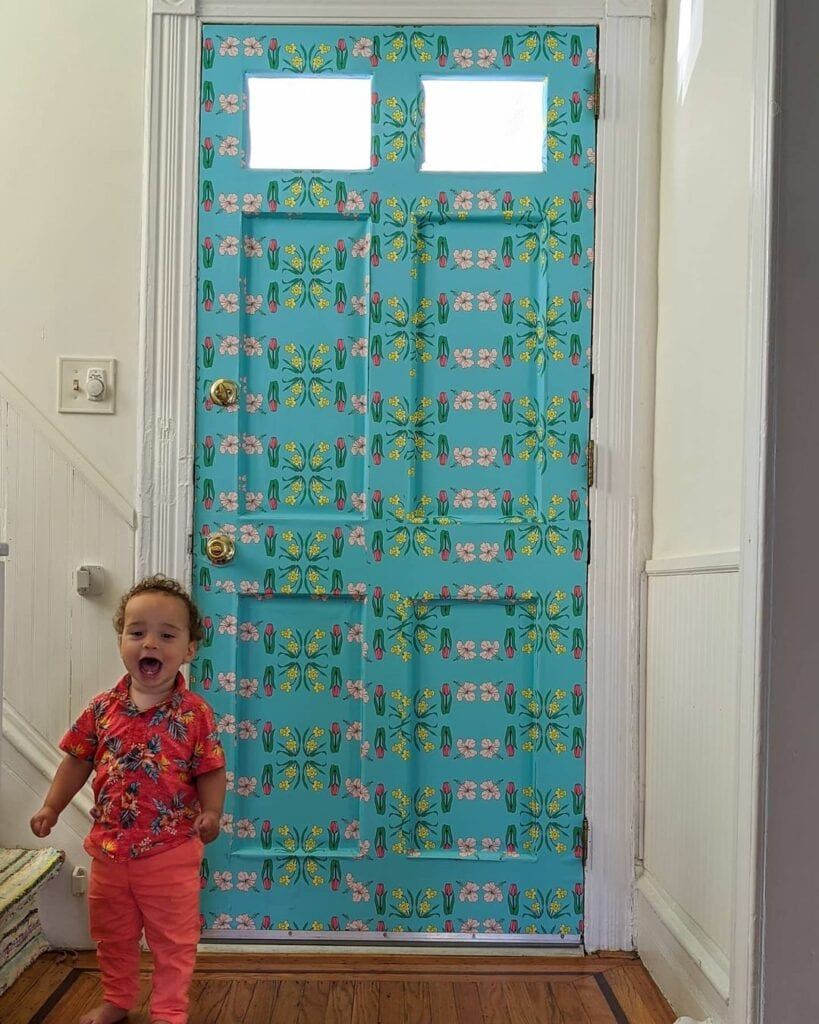 A child looks joyful in front of a bright blue patterned wallpapered door