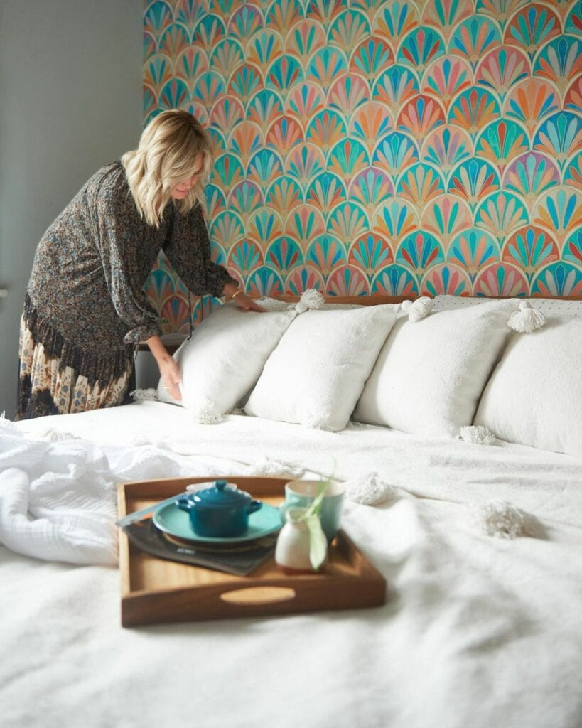A women arranges pillows on a bed in front of a wallpapered wall featuring a colorful pattern