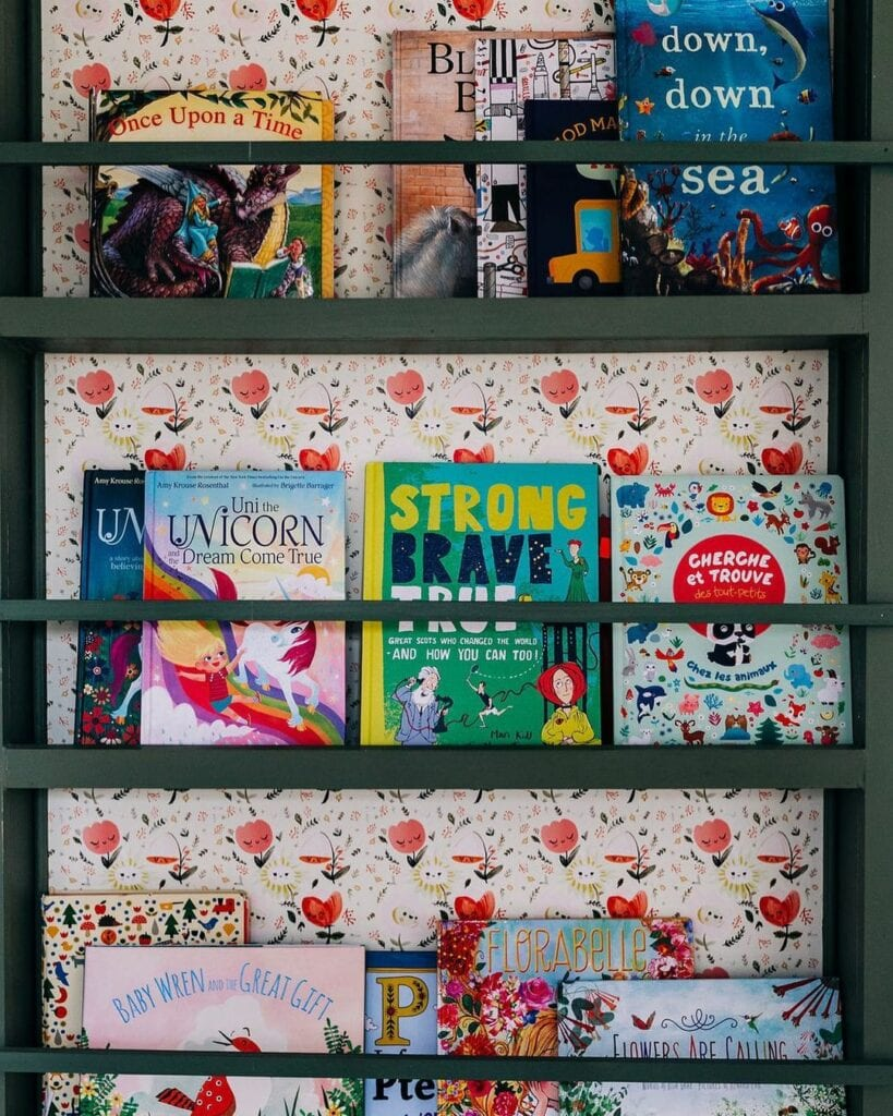 A kids bookshelf with a wallpapered back walls with a colorful playful design