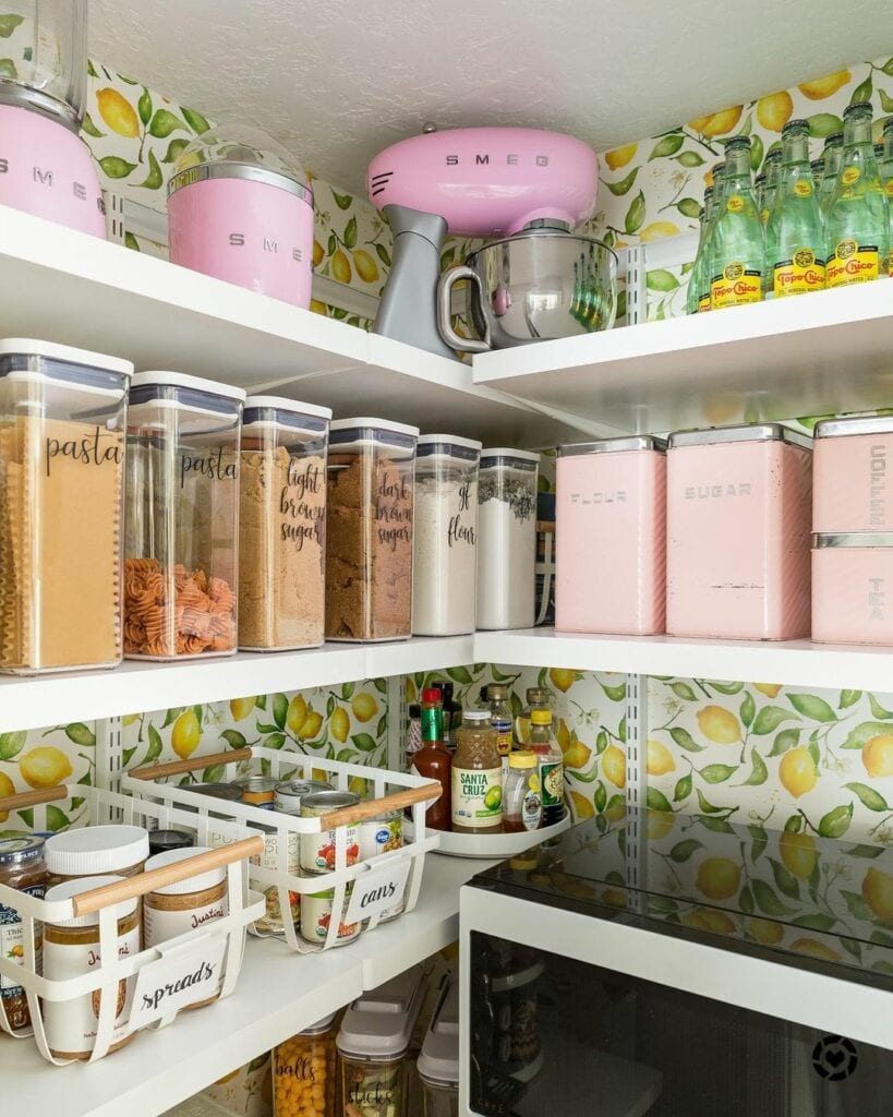 An organized pantry with pink accessories uses a lemon wallpaper