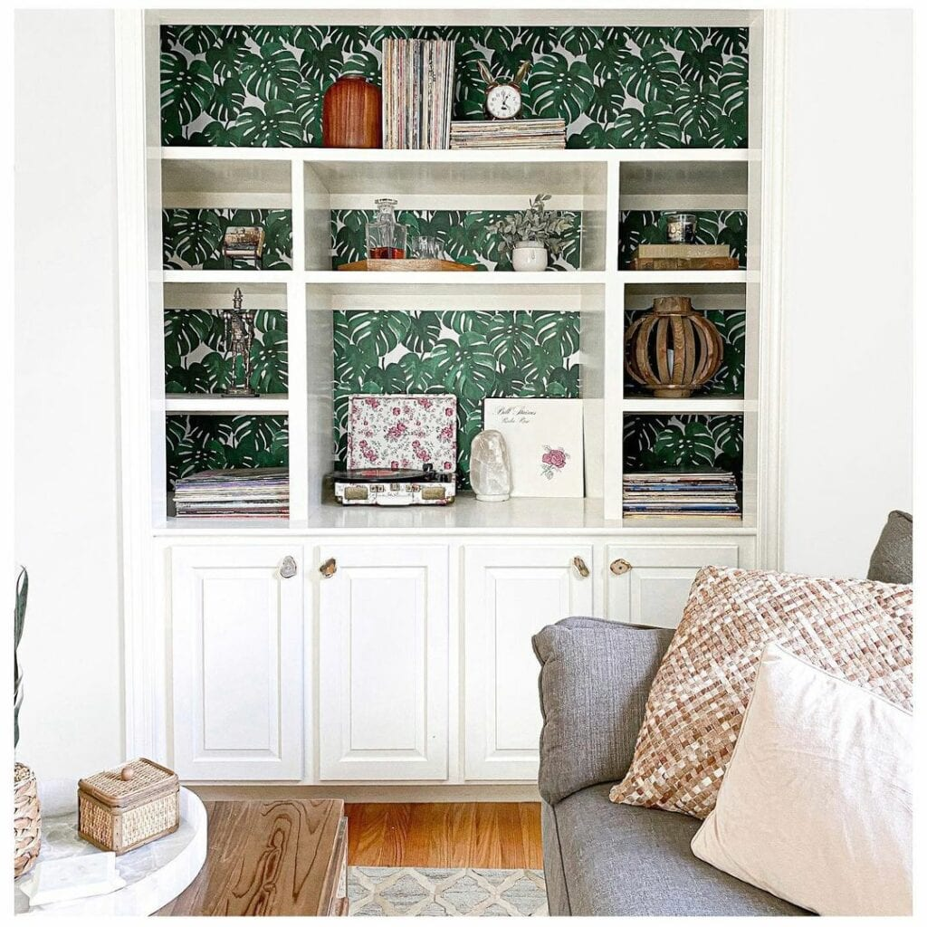A Green wallpaper featuring monstera leaves is used on the backing of a white bookcases