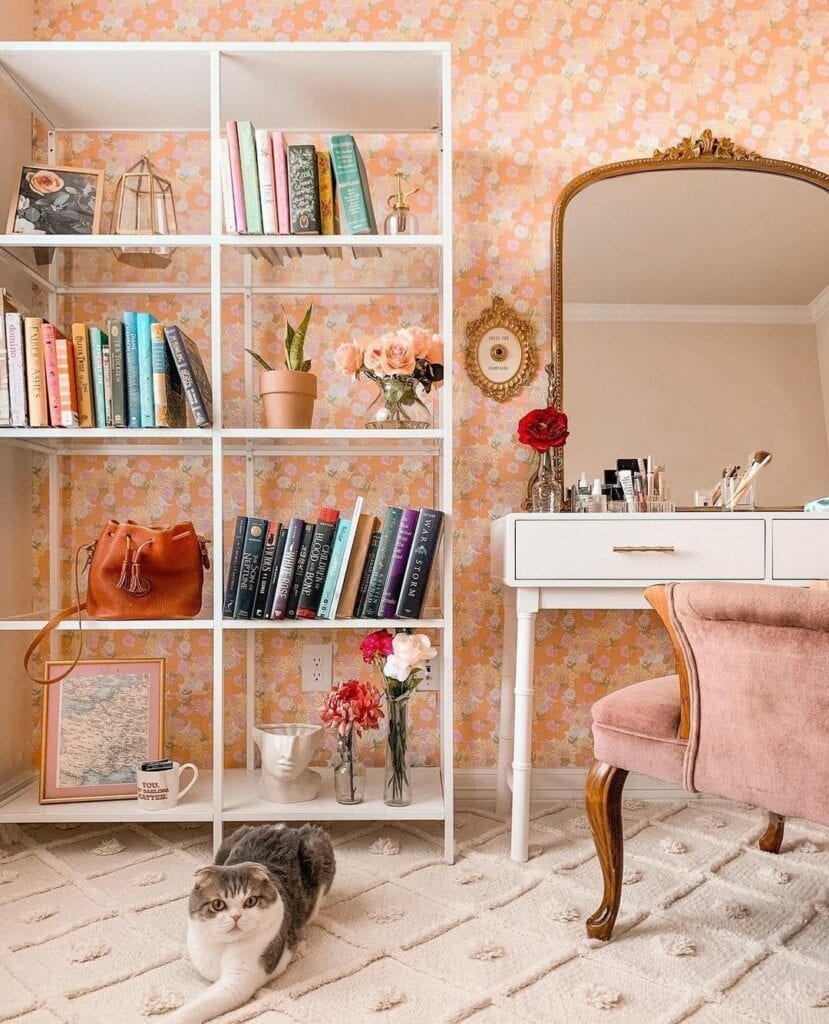 A room with a bookshelf, vanity and cat is wallpapered with a pink floral design