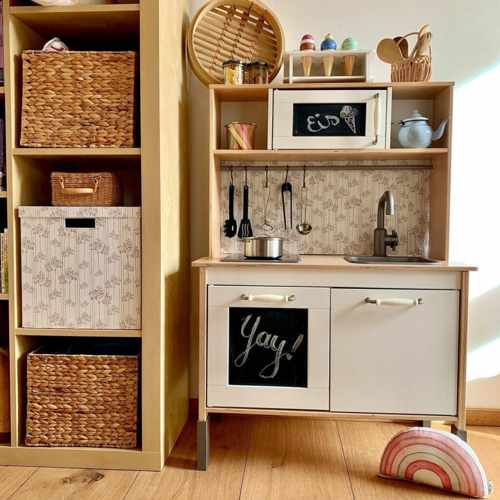 An Ikea kitchen kids play set has been wallpapered with a simple floral white and brown floral design