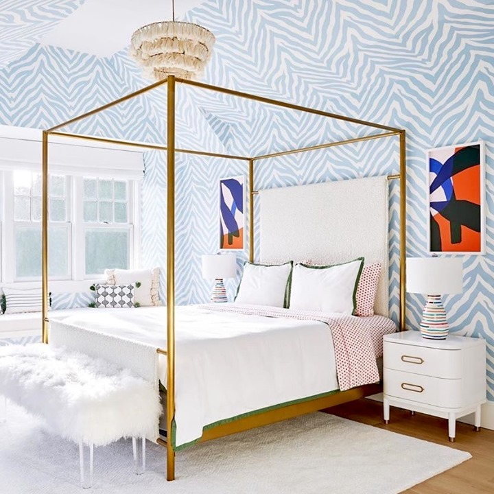 A bedroom features a blue and white zebra print wallpaper on the walls and ceiling