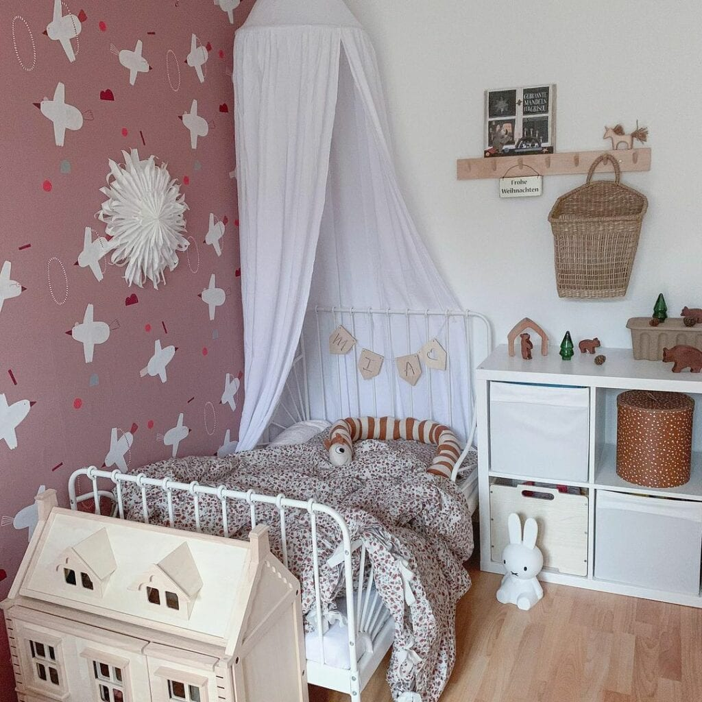 A kids bedroom with a wallpapered accent wall featuring birds and shapes