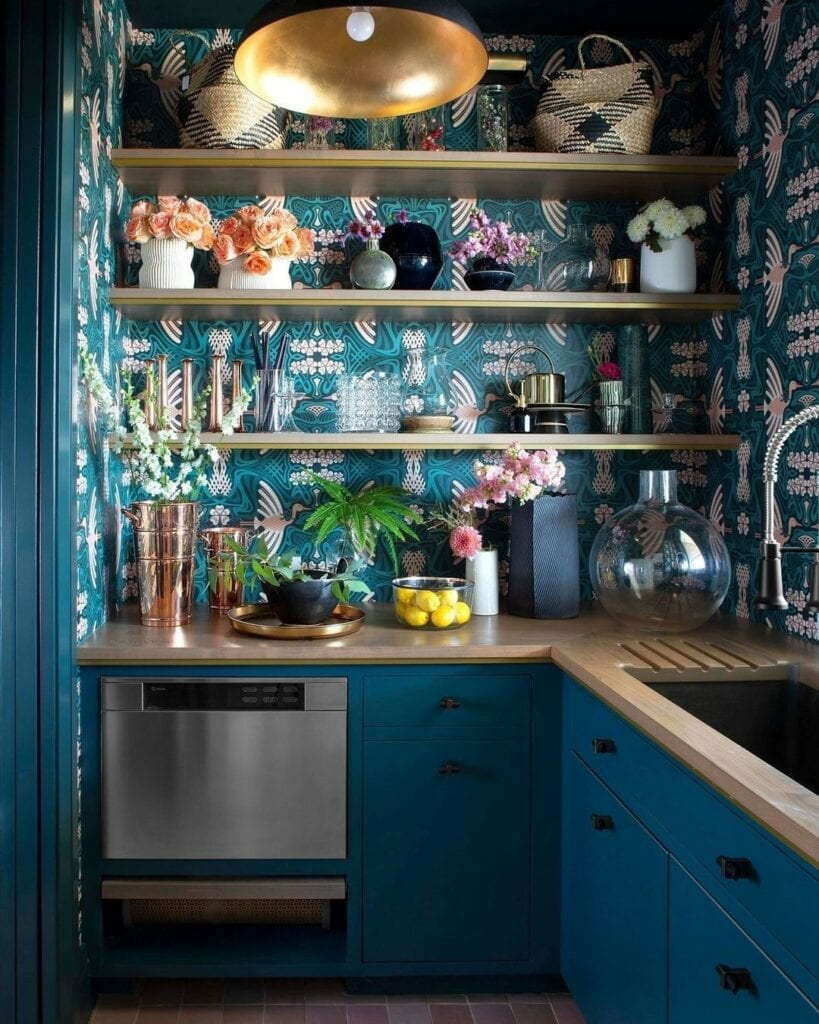 A kitchen wall with shelving uses a bold green blue patterned wallpaper