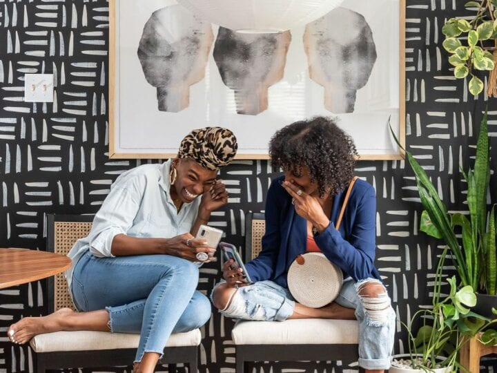 Two women sit on chairs and laugh at a cell phone in front of a black and white patterned wallpaper wall