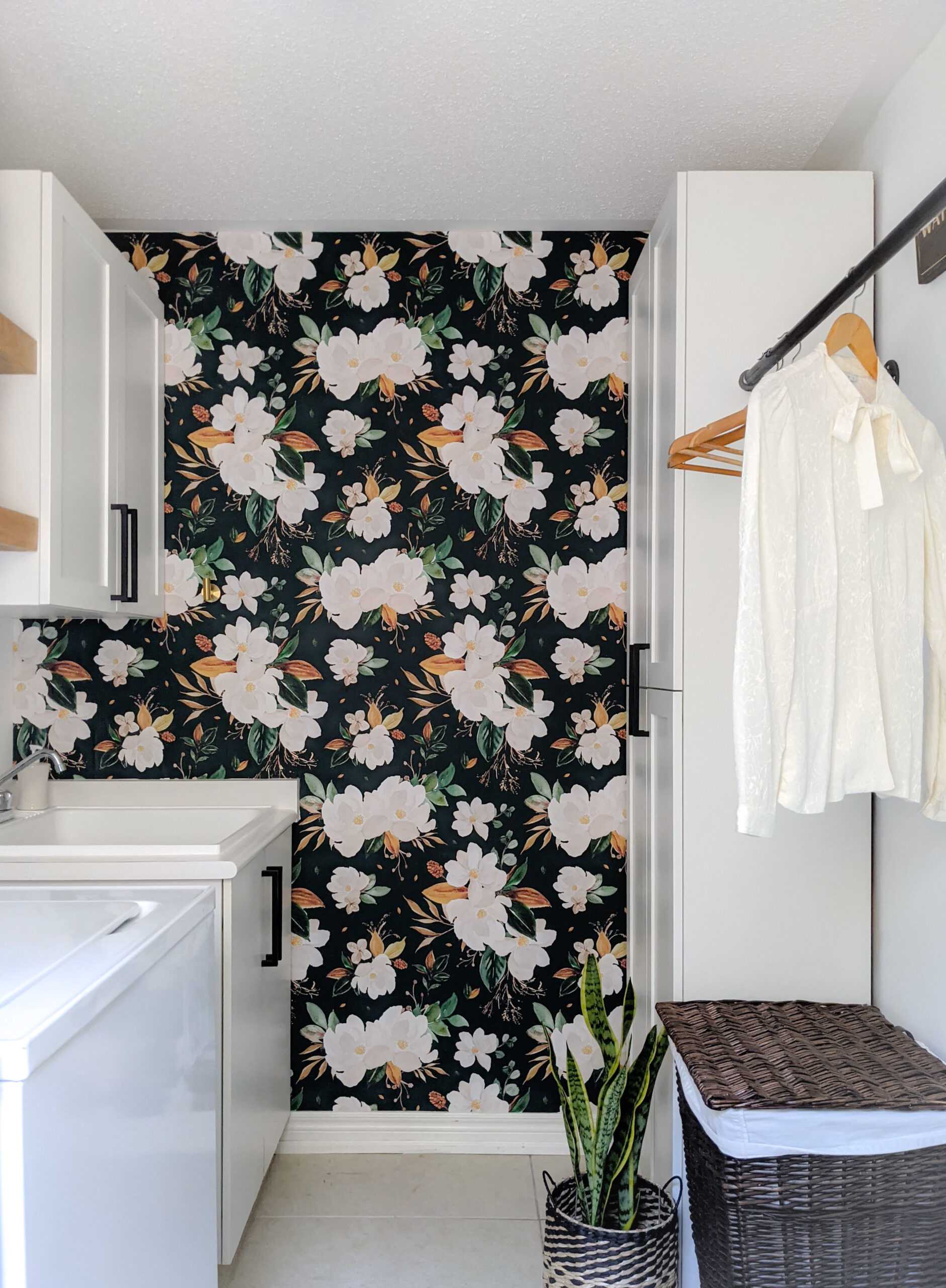 A laundry room with a dark floral wallpaper
