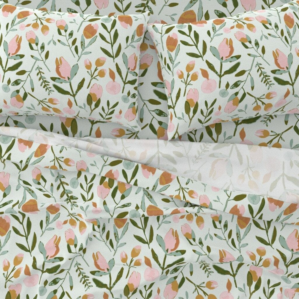 A topdown bedding view featuring pink tulips with a light green background