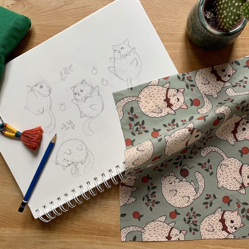 Pencil drawing of cat with floral accents next to the fabric printed with the illustration