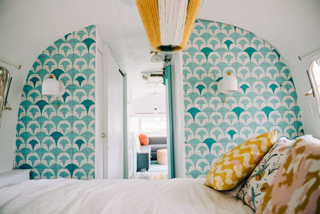 An airstream trailer bedroom featuring a teal and grey/beige geometric design wallpaper