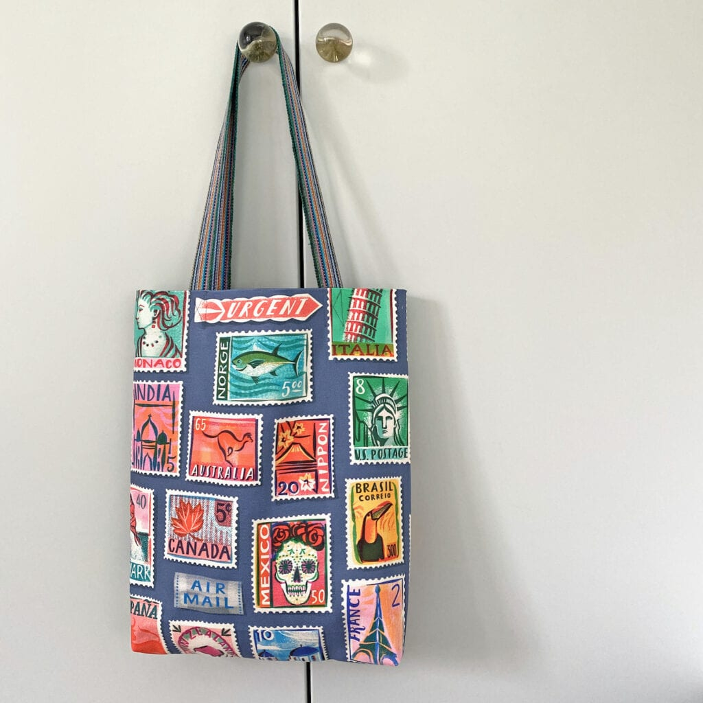 Tote bag made of a fabric with stamp illustrations hands on a door.