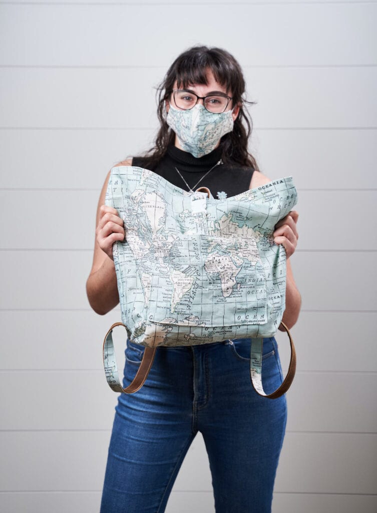 Ace holds up a backpack made of map fabric while wearing a matching mask