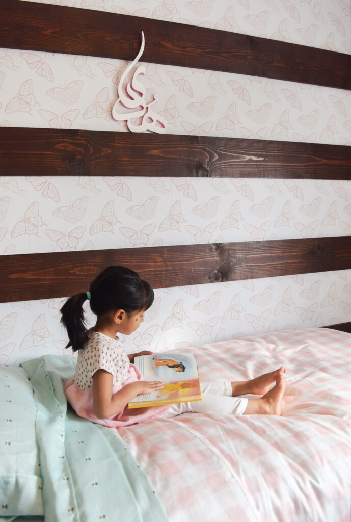 A girl reads a book on a bed in front of a wall wallpapered with a pink butterfly design.