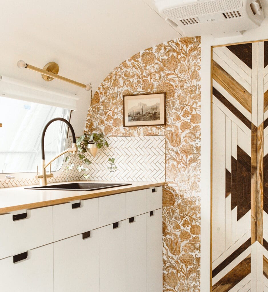 The kitchen of an airstream trailer featuring a brown vintage floral wallpaper