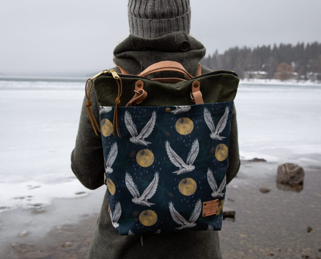 Person wearing a backpack featuring illustrations of owls and moons standing near a body of water with a forest in the distance