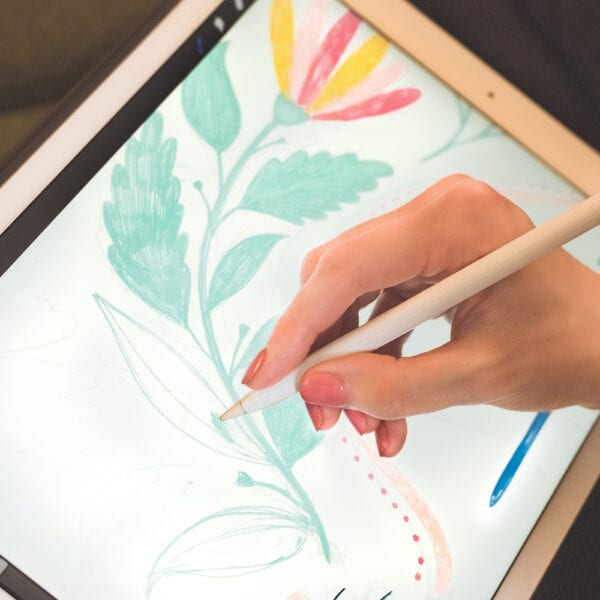 Artist works on a floral illustration with an Apple pencil and Ipad