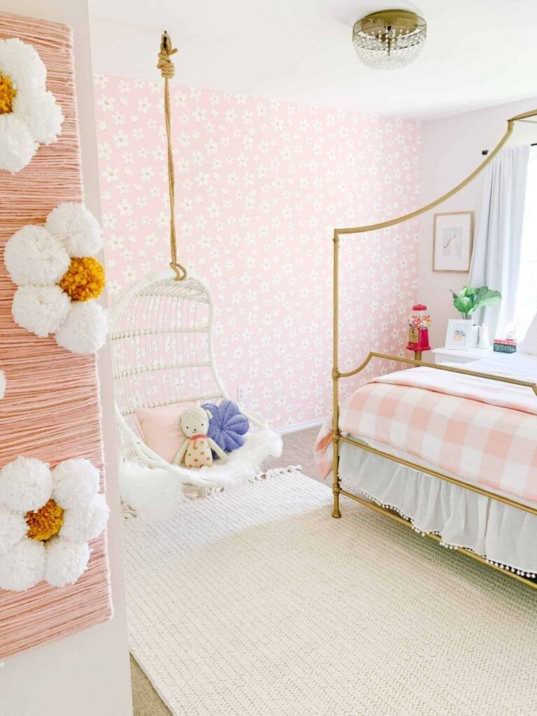 A children's bedroom with a bed and hanging chair featuring a pink and white daisy wallpaper