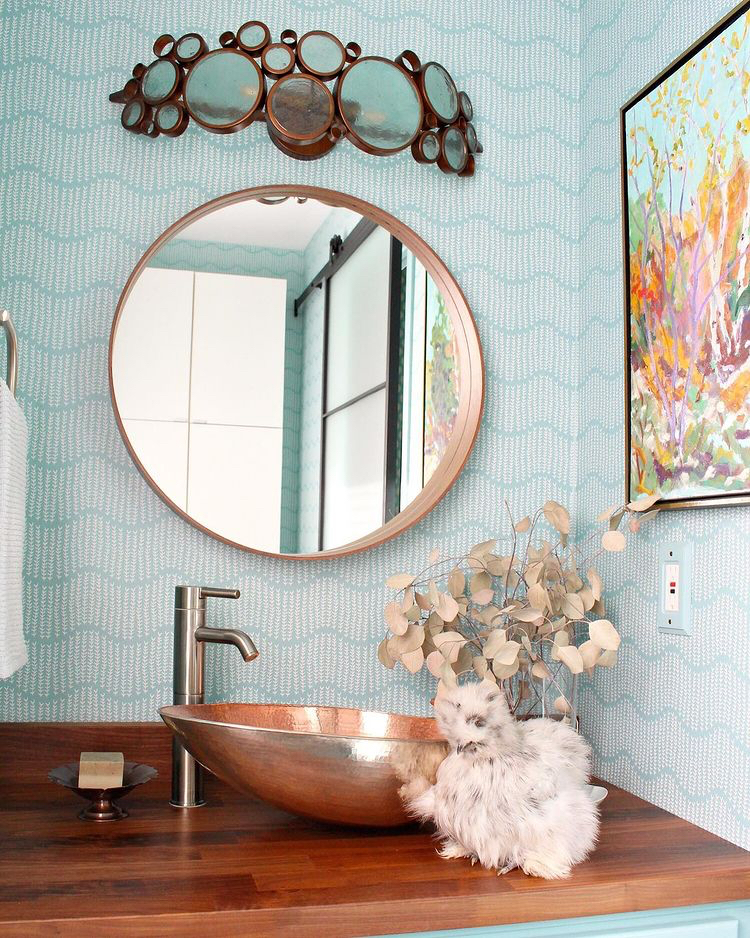 A bathroom sink with a chicken nearby features a teal and white design wallpaper