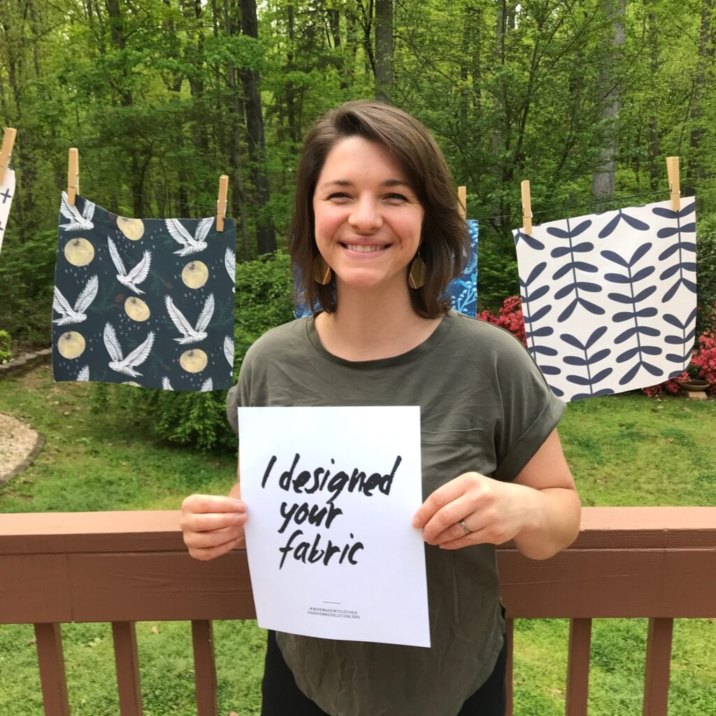 "Katie holds a piece of paper that says ""I deigned your fabric"" in front fabric swatches hanging off of a clothesline"
