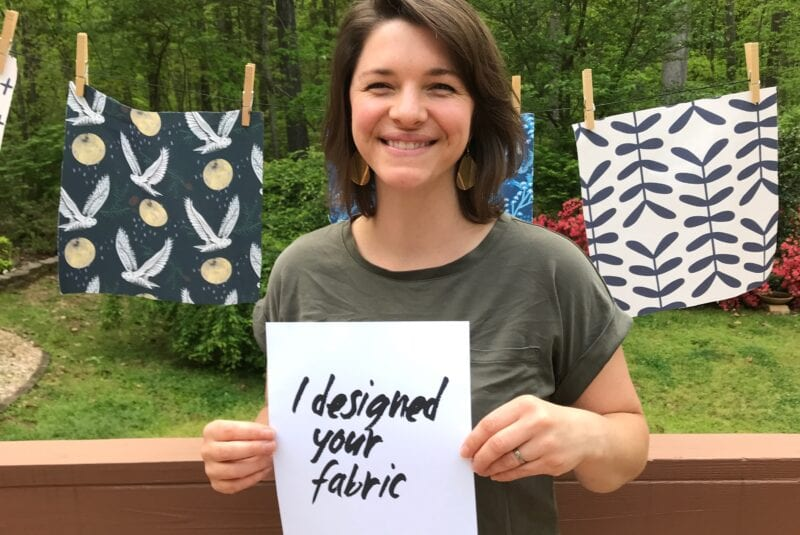 """Katie stands in front of a clotheslines with her fabric swatches holding a sign that says """"I designed your fabric"""""""
