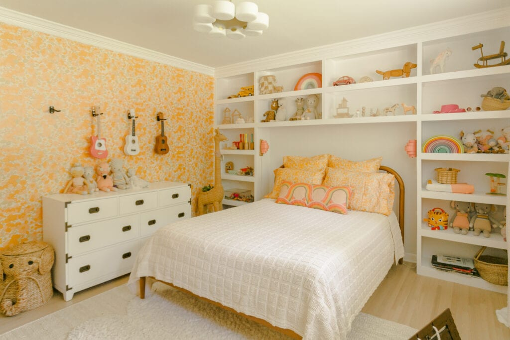 A children's room with built-in shelving features an orange floral wallpaper