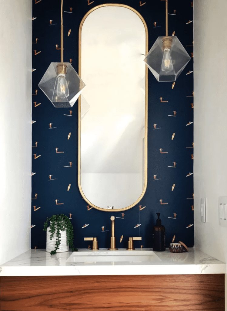 A bathroom sink with a tall oval mirror and geometric hanging lights. The wall features a wallpaper design or small illustrator surfers on surf boards