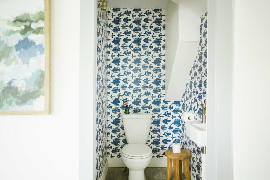 A bathroom features a blue and white bird wallpape
