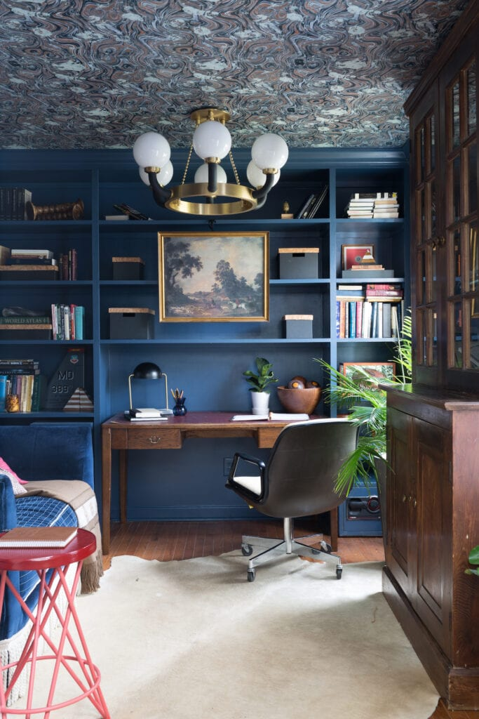 A blue office features a marble wallpaper on the ceiling